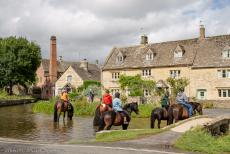 IMM 2019 Bristol -  Classic Car Road Trip: Horses in the river Eye, the Old Mill in Lower Slaughter in the background. In the 14th century, the mill became...