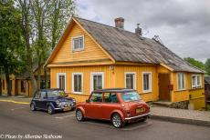 Lithuania 2015 - Classic Car Road Trip: Two Dutch classic minis in front of one of the wooden houses in the historic Town of Trakai in Lithuania. The...